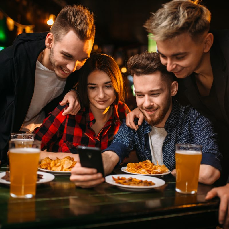 Fun company watches photo on phone in a sport bar, happy football fans
